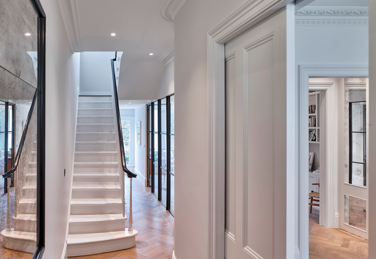 Image shows a pocket door kit using a white paneled door sliding back into the wall cavity. The background is a beautiful residential hallway with stairs and a large ornate mirror
